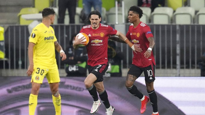 Manchester Uniteds Edinson Cavani, center, celebrates with his teammate Marcus Rashford after scoring his sides opening goal during the Europa League final soccer match between Manchester United and Villarreal in Gdansk, Poland, Wednesday, May 26, 2021. (AP Photo/Michael Sohn, Pool)