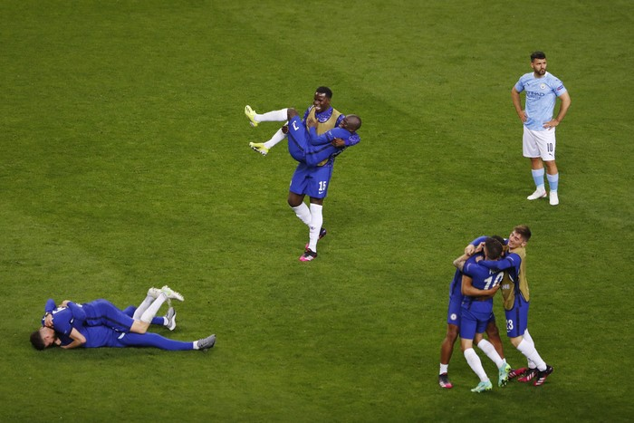 PORTO, PORTUGAL - MAY 29: Kurt Zouma, Ngolo Kante and teammates of Chelsea celebrate victory as Sergio Aguero of Manchester City looks dejected following the UEFA Champions League Final between Manchester City and Chelsea FC at Estadio do Dragao on May 29, 2021 in Porto, Portugal. (Photo by Susan Vera - Pool/Getty Images)