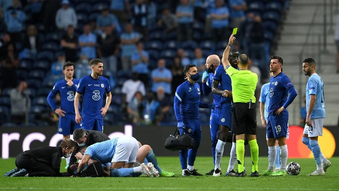 PORTO, PORTUGAL - MAY 29: Antonio Ruediger of Chelsea receives a yellow card as Kevin De Bruyne of Manchester City receives medical attention during the UEFA Champions League Final between Manchester City and Chelsea FC at Estadio do Dragao on May 29, 2021 in Porto, Portugal. (Photo by David Ramos/Getty Images)