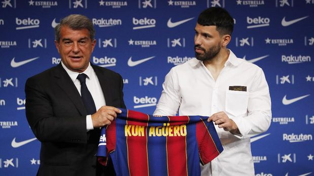 Soccer Football - FC Barcelona present new signing Sergio Aguero - Camp Nou, Barcelona, Spain - May 31, 2021 FC Barcelona's new signing Sergio Aguero holds his shirt with president Joan Laporta during the press conference REUTERS/Albert Gea