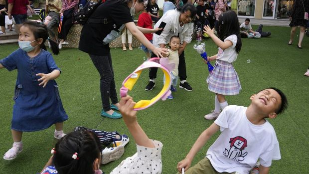 A child holds a dinosaur balloon during Children's Day at a mall in Beijing on Tuesday, June 1, 2021. China's ruling Communist Party said it will ease birth limits to allow all couples to have three children instead of two in hopes of slowing the rapid aging of its population, which is adding to strains on the economy and society. (AP Photo/Ng Han Guan)