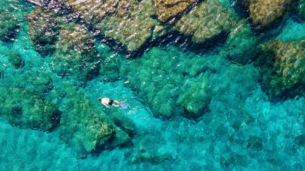 A man snorkeling in the emerald waters of the Aegean Sea in Andros island, Cyclades, Greece, during summer time