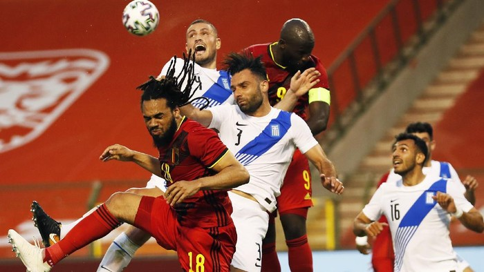 Belgiums Jason Denayer, left, goes up against Greeces Giorgos Tzavellas, third left, during the international friendly soccer match between Belgium and Greece at the King Baudouin stadium in Brussels, Thursday, June 3, 2021. (AP Photo/Francisco Seco)