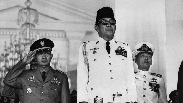 Indonesian President Ahmed Sukarno (C) attends a mass rally held at the Freedom Square in front of the Merdeka Palace, in Jakarta, 17 August 1966, to mark the Indonesia's 21st anniversary of Independance from the Dutch. The Indonesian Army strongman Mohamed Suharto (L) stands in attention in the background. (Photo by AFP)