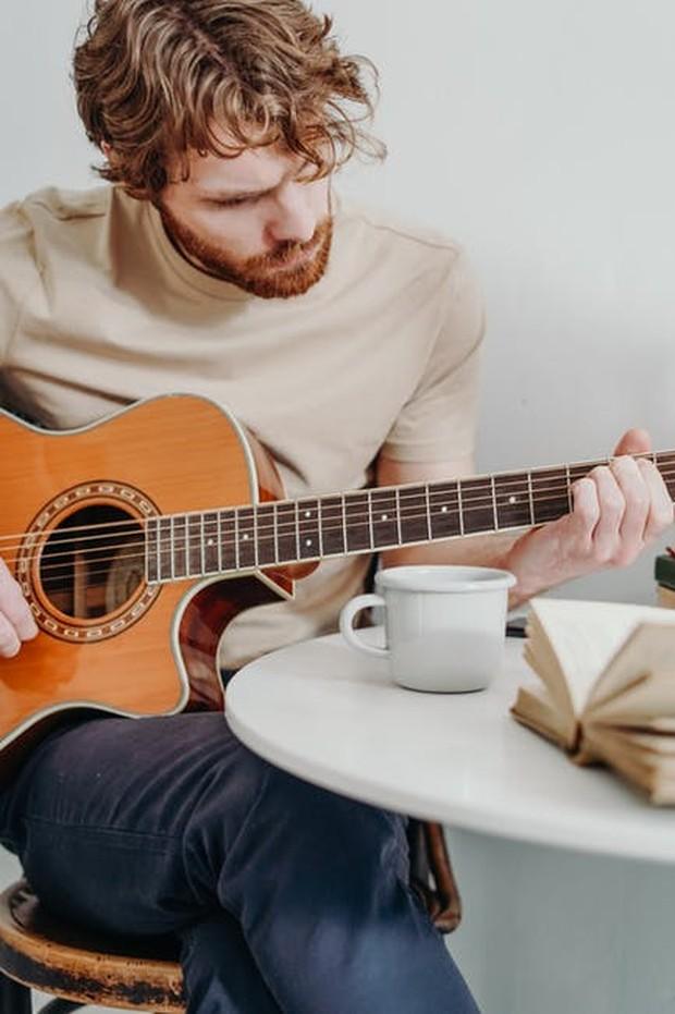 Seorang pria bermain gitar