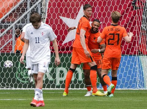 Netherlands' Wout Weghorst, rear left, and Netherlands' Frenkie de Jong, rear right, run to hug Netherlands' Memphis Depay who scored his side's first goal with a penalty during the friendly soccer match between The Netherlands and Georgia, in the run-up to the Euro2020 soccer tournament, in Enschede, eastern Netherlands, Sunday, June 6, 2021. (AP Photo/Peter Dejong)
