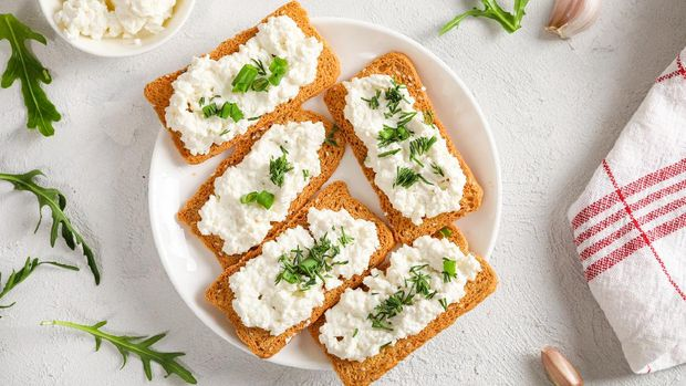 Crispy bread crackers with cottage cheese and green herb on plate on white background. Top view.