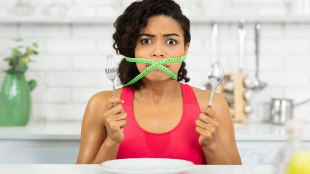 Diet Restriction Concept. Portrait of young frustrated black girl with a green measuring tape around her mouth