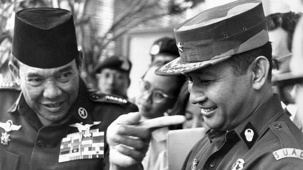 Indonesian President Ahmed Sukarno (L) is talking to strongman General Mohamed Suharto (R), after the disbanding session of the crush Malaysia command, 24 August 1966, in Jakarta. (Photo by - / PANASIA-FILES / AFP)