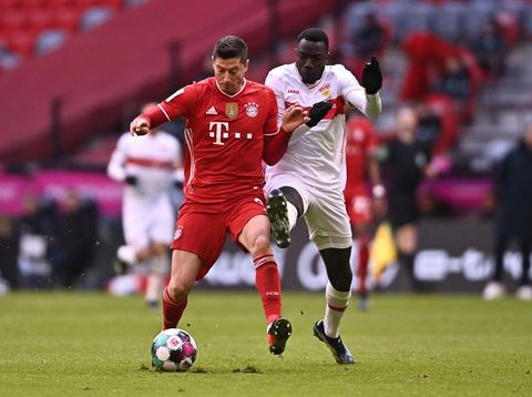 MUNICH, GERMANY - MARCH 20: Robert Lewandowski of FC Bayern Muenchen is challenged by Silas Wamangituka of VfB Stuttgart  during the Bundesliga match between FC Bayern Muenchen and VfB Stuttgart at Allianz Arena on March 20, 2021 in Munich, Germany. Sporting stadiums around Germany remain under strict restrictions due to the Coronavirus Pandemic as Government social distancing laws prohibit fans inside venues resulting in games being played behind closed doors. (Photo by Lukas Barth-Tuttas - Pool/Getty Images)