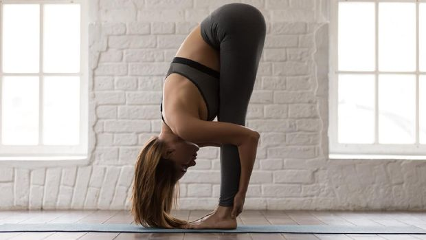 Beautiful woman practicing yoga, standing in uttanasana pose, forward bend, head to knees exercise, attractive sporty girl in grey sportswear, pants and bra working out at home or in yoga studio