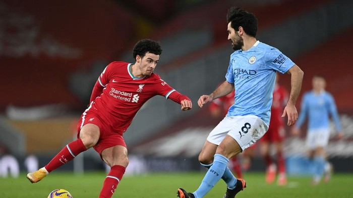 LIVERPOOL, ENGLAND - FEBRUARY 07: Curtis Jones of Liverpool controls the ball under pressure from Ilkay Gundogan of Manchester City during the Premier League match between Liverpool and Manchester City at Anfield on February 07, 2021 in Liverpool, England. Sporting stadiums around the UK remain under strict restrictions due to the Coronavirus Pandemic as Government social distancing laws prohibit fans inside venues resulting in games being played behind closed doors. (Photo by Laurence Griffiths/Getty Images)