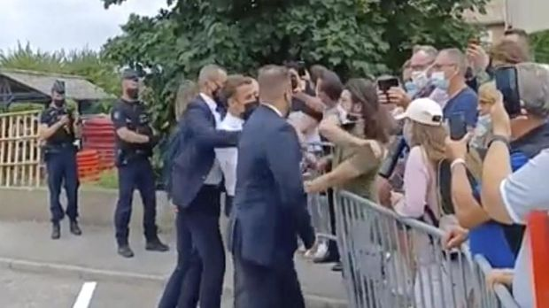 In this grab taken from video France's President Emmanuel Macron, centre, is slapped by a man, in green T-shirt, during a visit to Tain-l'Hermitage, in France, Tuesday, June 8, 2021. Macron denounced