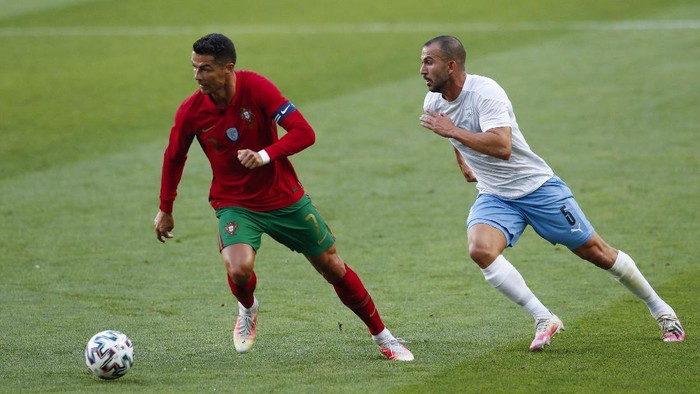 Portugals Cristiano Ronaldo, left, runs with the ball next to Israels Orel Dgani during the international friendly soccer match between Portugal and Israel at the Alvalade stadium in Lisbon, Wednesday, June 9, 2021. (AP Photo/Armando Franca)