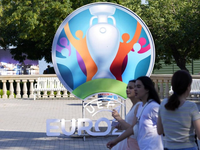 People walk past sign promoting the upcoming Euro 2020 soccer championship in Baku, Azerbaijan, Thursday, June 10, 2021. The Euro 2020 gets underway on Friday June 11 and is being played in 11 host cities across 11 countries. The event was delayed by one year after being postponed in 2020 due to the COVID-19 pandemic. (AP Photo/Darko Vojinovic)
