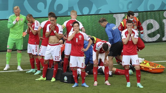 Denmarks players react as their teammate Christian Eriksen lays injured on the ground during the Euro 2020 soccer championship group B match between Denmark and Finland at Parken stadium in Copenhagen, Denmark, Saturday, June 12, 2021. (Wolfgang Rattay/Pool via AP)