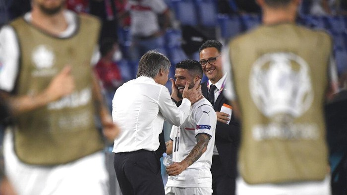 Italys Lorenzo Insigne, right, celebrates with Italys manager Roberto Mancini after scoring his sides third goal during the Euro 2020 soccer championship group A match between Italy and Turkey at the Olympic stadium in Rome, Friday, June 11, 2021. (Alberto Lingria/Pool Photo via AP)