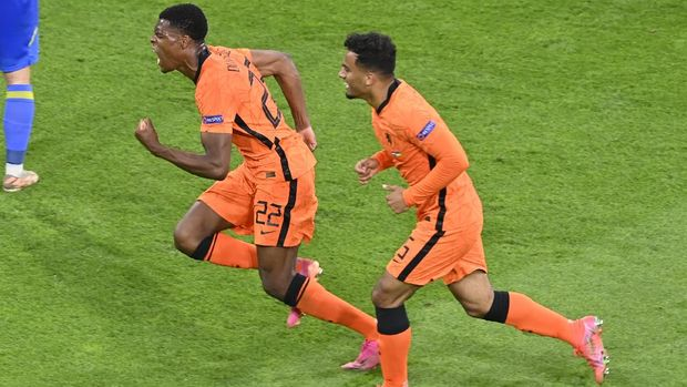 Netherlands' Denzel Dumfries, left, celebrates scoring their third goal during the Euro 2020 soccer championship group C match between Netherlands and Ukraine at Johan Cruijff Arena in Amsterdam, Netherlands, Sunday, June 13, 2021. (AP Photo/Olaf Kraak, Pool)