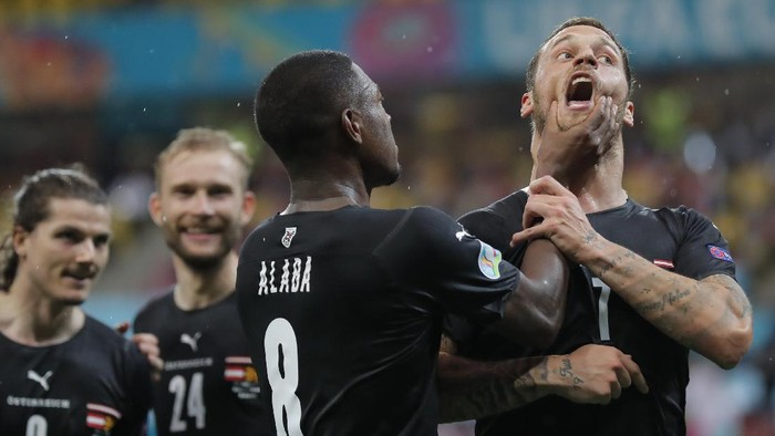 Austrias Marko Arnautovic, right, celebrates with Austrias David Alaba after scoring his sides third goal during the Euro 2020 soccer championship group C match between Austria and Northern Macedonia at the National Arena stadium in Bucharest, Romania, Sunday, June 13, 2021. (Robert Ghement/Poolvia AP)