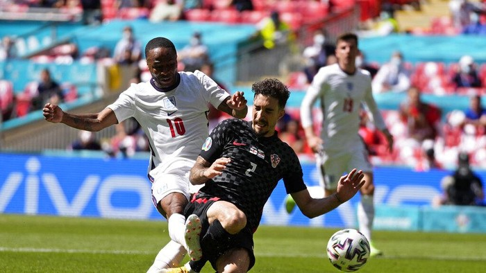 Englands Raheem Sterling, left, scores the opening goal past Croatias Sime Vrsaljko during the Euro 2020 soccer championship group D match between England and Croatia at Wembley stadium in London, Sunday, June 13, 2021. (AP Photo/Frank Augstein, Pool)