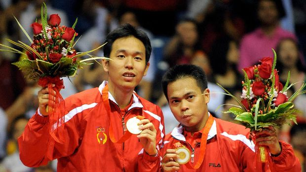 Markis Kido (R) and Hendra Setiawan of Indonesia celebrate with their gold medals in the men's badminton doubles event of the 2008 Beijing Olympic Games in Beijing on August 16, 2008.  Kido and Setiawan beat Cai Yun and Fu Haifeng of China 12-21, 21-11, 21-16.       AFP PHOTO/GOH CHAI HIN (Photo by GOH CHAI HIN / AFP)