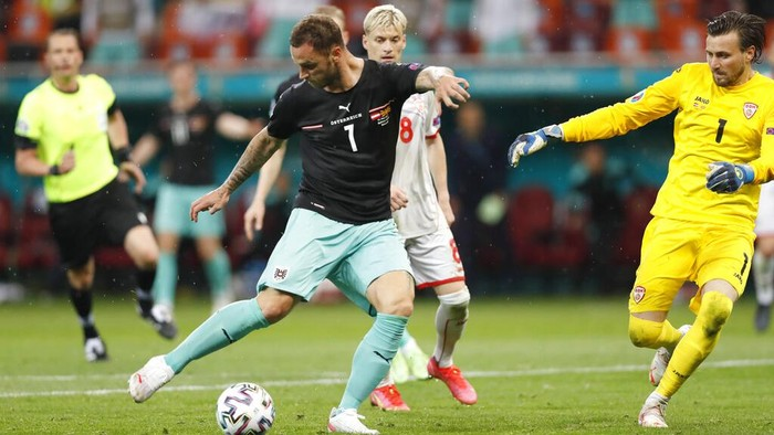 Austria's Marko Arnautovic, left, scores his side's third goal during the Euro 2020 soccer championship group C match between Austria and Northern Macedonia at the National Arena stadium in Bucharest, Romania, Sunday, June 13, 2021. (Robert Ghement/Poolvia AP)