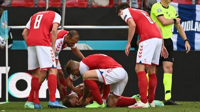 Denmark players help Denmark's midfielder Christian Eriksen after he collapsed before the medics arrive during the UEFA EURO 2020 Group B football match between Denmark and Finland at the Parken Stadium in Copenhagen on June 12, 2021. (Photo by Jonathan NACKSTRAND / various sources / AFP)