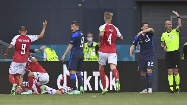 Referee Anthony Taylor, right, calls for medics to enter the field after Denmark's Christian Eriksen collapsed on the pitch during the Euro 2020 soccer championship group B match between Denmark and Finland at Parken Stadium in Copenhagen, Saturday, June 12, 2021. (Stuart Franklin/Pool via AP)