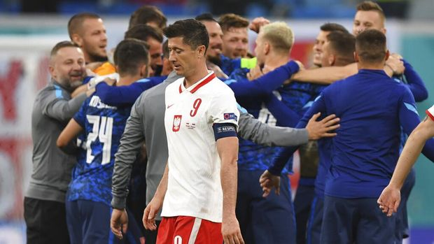 Poland's Robert Lewandowski, centre, walks as Slovakia players celebrate their victory after the Euro 2020 soccer championship group E match between Poland and Slovakia at Gazprom arena stadium in St. Petersburg, Russia, Monday, June 14, 2021. (Kirill Kudryavtsev/Pool via AP)