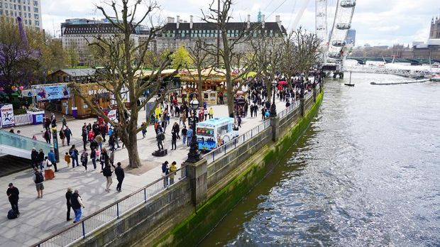 London, England, UK - April 17, 2016: People enjoying the fair ground atmosphere at London Southbank by the river Thames on a sunny Spring day.