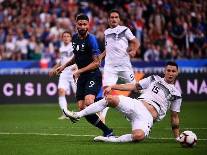 Germanys defender Niklas Suele (R) falls past Frances forward Olivier Giroud during the UEFA Nations League football match between France and Germany at the Stade de France in Saint-Denis, near Paris on October 16, 2018. (Photo by FRANCK FIFE / AFP)