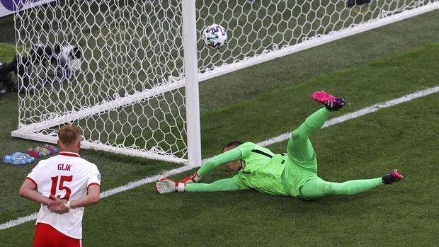 Poland's goalkeeper Wojciech Szczesny scores an own goal during the Euro 2020 soccer championship group E match between Poland and Slovakia at Gazprom arena stadium in St. Petersburg, Russia, Monday, June 14, 2021. (Anton Vaganov/Pool via AP)