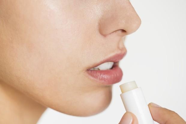 Ilustrasi menggunakan pelembap bibir.