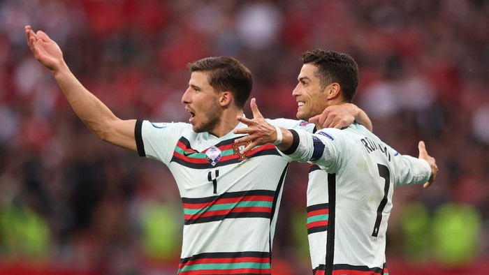 BUDAPEST, HUNGARY - JUNE 15: Cristiano Ronaldo of Portugal celebrates with team mate Ruben Dias after scoring their sides third goal during the UEFA Euro 2020 Championship Group F match between Hungary and Portugal at Puskas Arena on June 15, 2021 in Budapest, Hungary. (Photo by Alex Pantling/Getty Images)