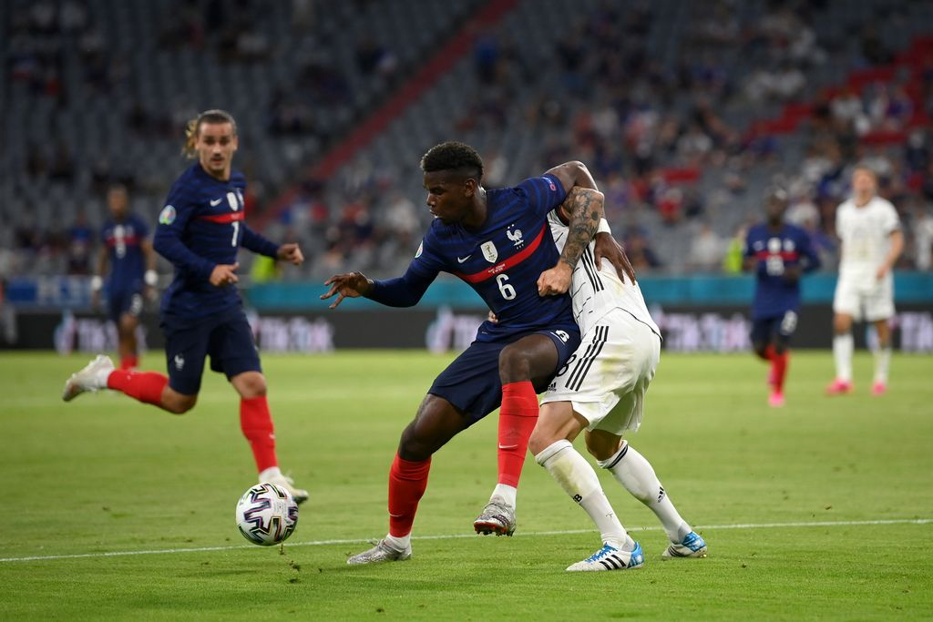 MUNICH, GERMANY - JUNE 15: Paul Pogba of France is challenged by Toni Kroos of Germany during the UEFA Euro 2020 Championship Group F match between France and Germany at Football Arena Munich on June 15, 2021 in Munich, Germany. (Photo by Matthias Hangst/Getty Images)