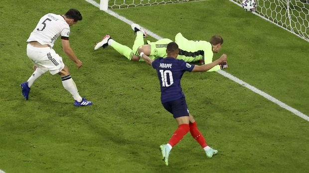 France's Kylian Mbappe, right, celebrates after Germany's Mats Hummels, left, scored an own goal during the Euro 2020 soccer championship group F match between France and Germany at the Allianz Arena stadium in Munich, Tuesday, June 15, 2021. (AP Photo/Alexander Hassenstein, Pool)
