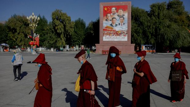 Buddhist nuns walk past a poster showing Chinese President Xi Jinping and former leaders Jiang Zemin, Mao Zedong, Deng Xiaoping and Hu Jintao in Lhasa during a government-organised tour of the Tibet Autonomous Region, China, October 15, 2020.  Picture taken October 15, 2020.  REUTERS/Thomas Peter  REFILE - CORRECTING FAMILY NAMES