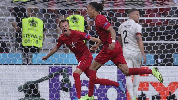 Denmark's Yussuf Poulsen, right, celebrates after scoring his side's first goal during the Euro 2020 soccer championship group B match between Denmark and Belgium at Parken stadium in Copenhagen, Thursday, June 17, 2021. (Friedemann Vogel/Pool via AP)