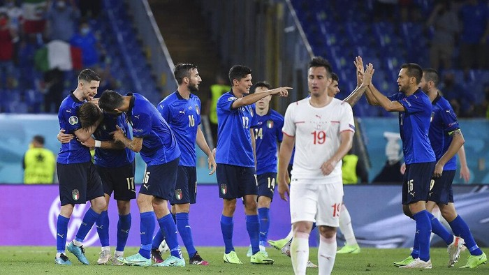 Italys Ciro Immobile, covered by his teammates, celebrates after scoring his sides third goal during the Euro 2020 soccer championship group A match between Italy and Switzerland at Olympic stadium in Rome, Wednesday, June 16, 2021. (Ettore Ferrari, Pool via AP)