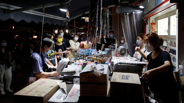 People line up to purchase Apple Daily newspaper from a newspaper stall after police raided its newsroom and arrested five executives the day before, in Hong Kong, China early June 18, 2021. REUTERS/James Pomfret