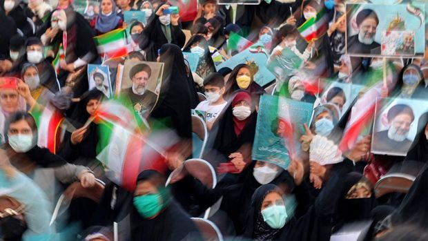 Supporters of Iranian presidential candidate Ebrahim Raisi attend an election campaign rally in the capital Tehran, on June 14, 2021. (Photo by ATTA KENARE / AFP)