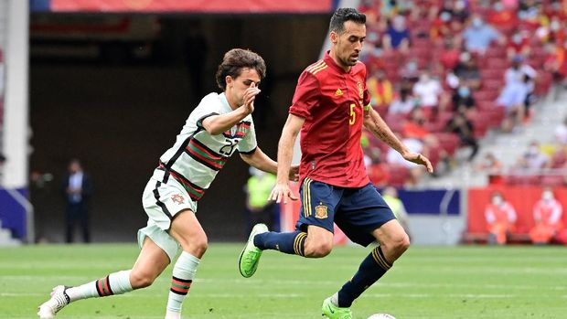 Portugal's forward Joao Felix (L) vies with Spain's midfielder Sergio Busquets during the international friendly football match between Spain and Portugal at the Wanda Metropolitano stadium in Madrid in preperation for the UEFA European Championships, on June 4, 2021. (Photo by JAVIER SORIANO / AFP)