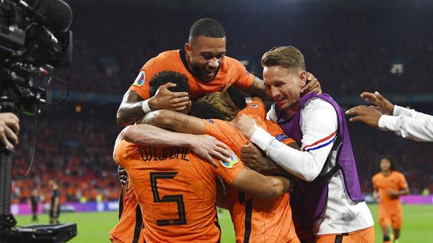 Denzel Dumfries, covered by his teammates, of the Netherlands celebrates after scoring his side's second goal during the Euro 2020 soccer championship group C match between the The Netherlands and Austria at Johan Cruijff ArenA in Amsterdam, Netherlands, Thursday, June 17, 2021. (John Thys, Pool via AP)