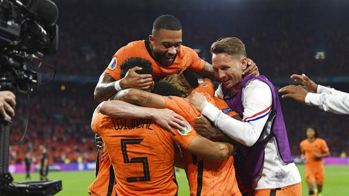 Denzel Dumfries, covered by his teammates, of the Netherlands celebrates after scoring his sides second goal during the Euro 2020 soccer championship group C match between the The Netherlands and Austria at Johan Cruijff ArenA in Amsterdam, Netherlands, Thursday, June 17, 2021. (John Thys, Pool via AP)