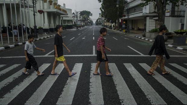 Sejumlah anak menyeberang di ruas jalan protokol kawasan Asia Afrika yang ditutup di Bandung, Jawa Barat, Jumat (18/6/2021). Warga menikmati suasana ruas jalan protokol di Kota Bandung yang lengang setelah ditutup untuk menekan peningkatan kasus aktif COVID-19 dan status siaga satu kawasan Bandung Raya. ANTARA FOTO/Novrian Arbi/rwa.