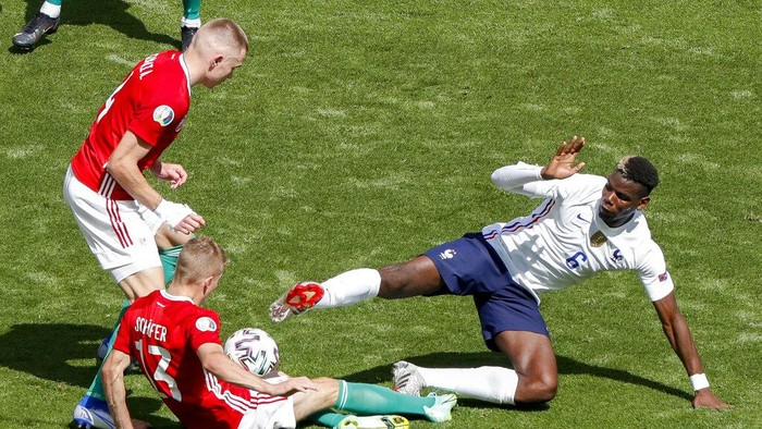 Frances Paul Pogba, right, slides in to kick the ball as Hungarys Andras Schaefer and Attila Szalai, left, watch during the Euro 2020 soccer championship group F match between Hungary and France at the Ferenc Puskas stadium in Budapest, Hungary, Saturday, June 19, 2021. (AP Photo/Laszlo Balogh,Pool)