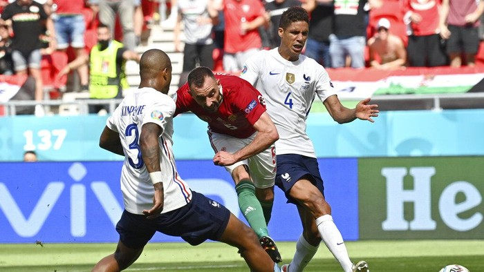 Frances Raphael Varane, right, and Frances Presnel Kimpembe, left, fail to stop Hungarys Attila Fiola from scoring his sides first goal during the Euro 2020 soccer championship group F match between Hungary and France at the Ferenc Puskas stadium in Budapest, Hungary Saturday, June 19, 2021. (Tibor Illyes/Pool via AP)