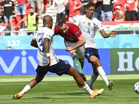 France's Raphael Varane, right, and France's Presnel Kimpembe, left, fail to stop Hungary's Attila Fiola from scoring his sides first goal during the Euro 2020 soccer championship group F match between Hungary and France at the Ferenc Puskas stadium in Budapest, Hungary Saturday, June 19, 2021. (Tibor Illyes/Pool via AP)
