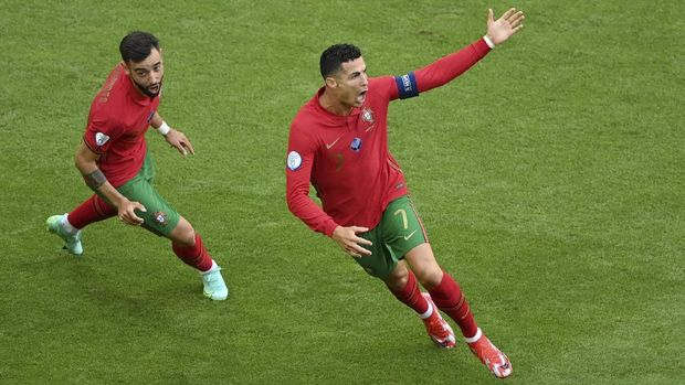 Portugal's Cristiano Ronaldo, right, celebrates after scoring his side's opening goal during the Euro 2020 soccer championship group F match between Portugal and Germany at the football arena stadium in Munich, Saturday, June 19, 2021. (Matthias Hangst/Pool Photo via AP)