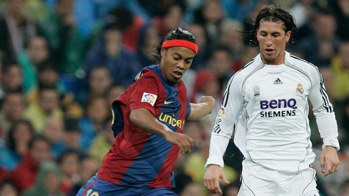 MADRID, SPAIN - OCTOBER 22: Ronaldinho (L) of Barcelona passes the ball beside Sergio Ramos of Real Madrid during the Primera Liga match between Real Madrid and Barcelona at the Santiago Bernabeu stadium on October 22, 2006 in Madrid, Spain  (Photo by Denis Doyle/Getty Images)